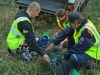 Etsintäharjoituksessa mukana ollut maalihenkilö on löydetty, hän esittää jalkansa pahasti loukannutta. Ambulanssi ei pääsisi lähellekään löytöpaikkaa, joten henkilö valmistellaan kuljetettavaksi maastoautolla potilaansiirtoalustaan tuettuna.